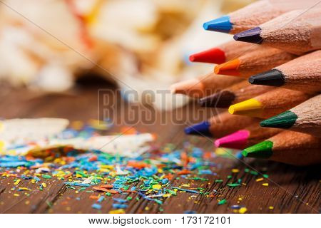 Pencil shavings and colored pencils on the wooden table. Art concept. Brown background. Painting and drawing. Design.