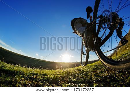 Detail of cyclist man feet riding mountain bike on outdoor trail in sunny meadow. Detail of the bicycle. Wheel. Legs and hand. Sunset. Low angle and fisheye. Green field in the countryside.