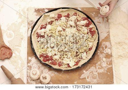 Preparing homemade Italian pizza cutting mushrooms. Kitchen