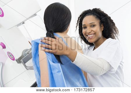 Happy Doctor Assisting Patient Undergoing Mammogram X-ray Test