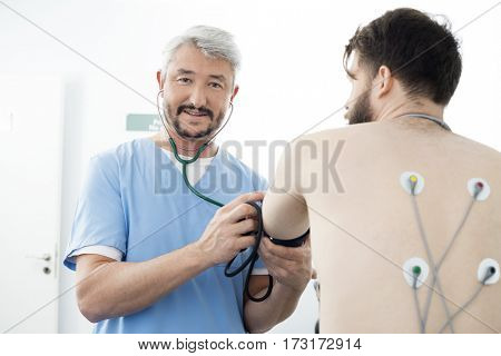 Portrait Of Doctor Measuring Blood Pressure Of Patient In Hospit