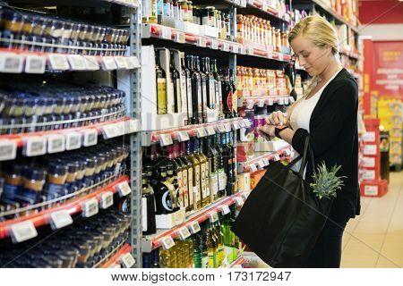 Woman Using Smart Watch In Supermarket