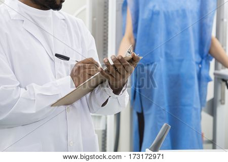 Midsection Of Male Radiologist Writing On Clipboard In Hospital
