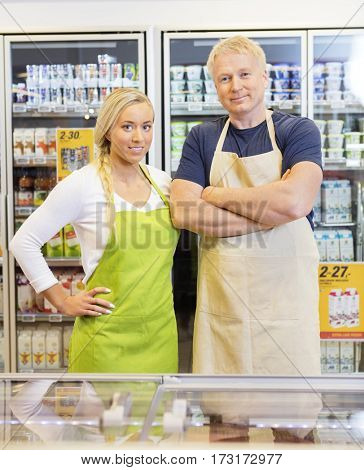 Confident Male And Female Workers In Supermarket
