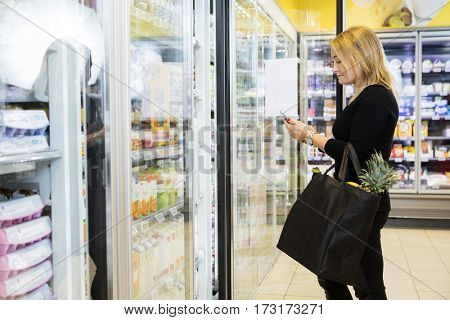 Mature Woman Using Mobile Phone While Carrying Shopping Bag