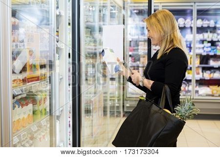 Mature Woman Holding Juice Packet In Grocery Store