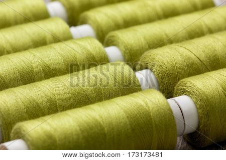 background of green spools of thread close-up