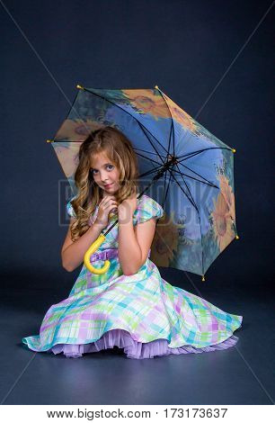 Girl sitting with an umbrella in his hands