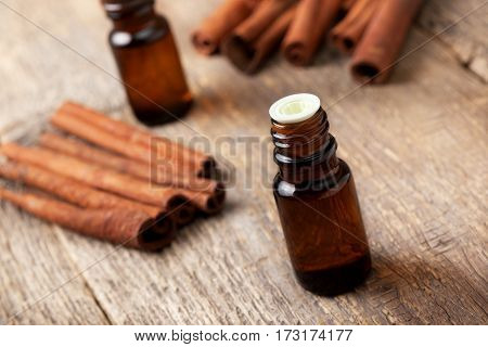 cinnamon essential oil in a glass bottle cinnamon sticks on old wooden background