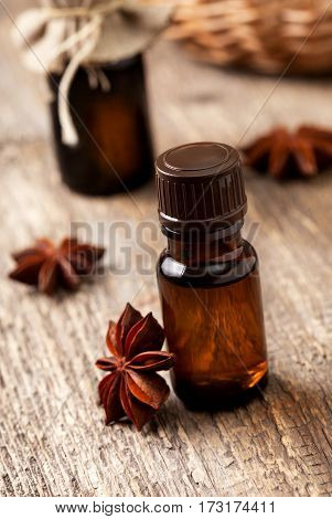 anise essential oil in glass bottles anise on old wooden background