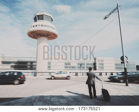 Silhouette of businessman with luggage standing near airport in front of air traffic control tower car and parking experienced male employer with suitcase waiting for taxi outdoors after work travel