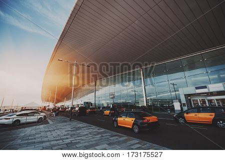 Cabstand in front of entrance of modern airport in Barcelona cabrank with a lot of taxies near glass facade of contemporary Airport terminal in Spain with road huge ceiling and parking lot
