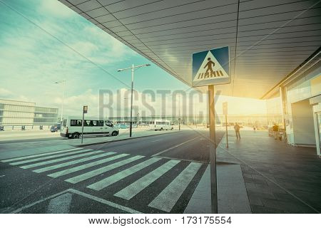 Pedestrian crossing area next to modern contemporary airport terminal entrance zebra traffic cross way with road sing with parking lot and small buses in distance on sunny day in Barcelona Spain