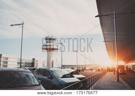 Parking lot road and cabstand near modern contemporary airport terminal in front of air traffic control tower with many passengers and staff passing in distance Barcelona Spain