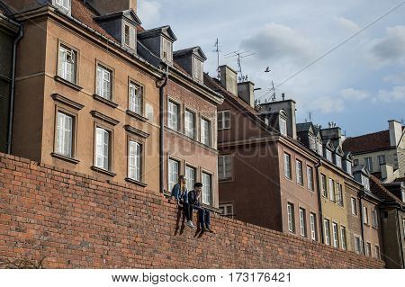 Love pair sitting on the wall in Warsaw Poland and look daydreaming in front of houses