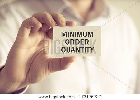 Businessman Holding Minimum Order Quantity Message Card