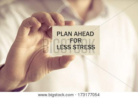 Businessman Holding Plan Ahead For Less Stress Message Card