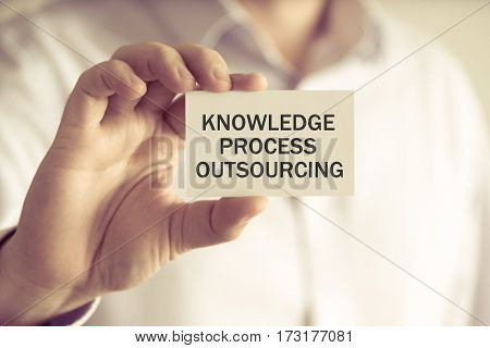 Businessman Holding Knowledge Process Outsourcing Message Card