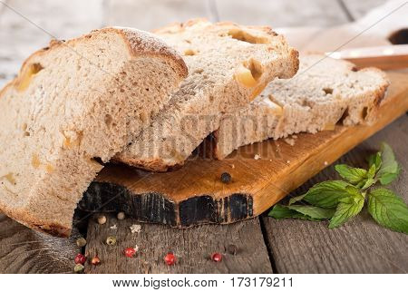 Sliced bread on cutting board and wooden background