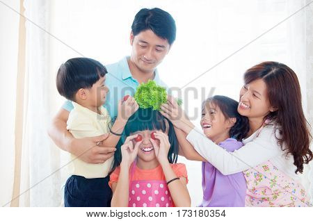 Asian family having fun in the kitchen with backlit lighting