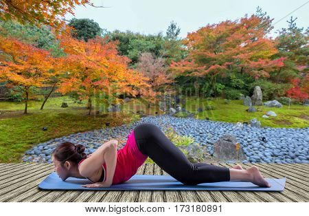 Sporty fit women practices yoga Anjaneyasana - low crescent lunge at autumn garden.