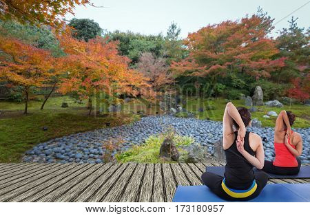 Two Sporty fit women practices yoga Anjaneyasana - low crescent lunge at autumn garden.