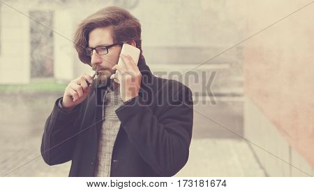 Young hipster man with a beard and glasses smokes an electronic cigarette. He says on his cell phone. Youth fashion. Delicious pairs. Cloud of steam. Business negotiations