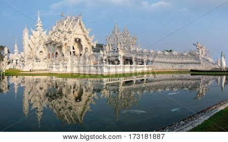 Magnificently grand white church and reflection in the water Rong Khun temple Chiang Rai province northern Thailand
