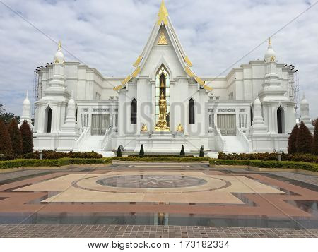 white church with gold Buddha statue in Thailand