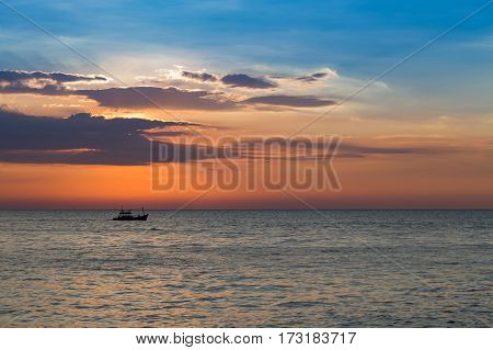 Beautiful sunset sky over seacoast skyline with small fishing boat in the ocean natural landscpae background