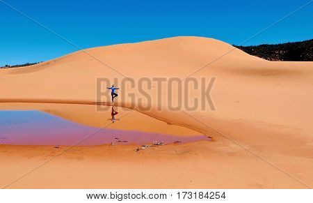Woman doing yoga on sand dunes. Coral Pink Sand Dunes State Park. Kanab. Cedar City. Utah. United States.