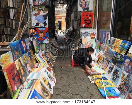 SHENZHEN CHINA -FEBRUARY 22 2017: Female artist sales her paintings on the street