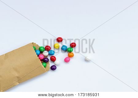 Bright, colorful gumballs spill from treat bag onto white open space for copy.