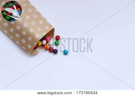 Bright, colorful gumballs spill onto white open space background.
