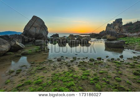 A rocky coastline sunrise with moss covered rocks looking out over the south China sea in Vung Lam Bay Vietnam.