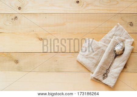 top view of one vintage spoon on a linen fabric on wooden boards background with copy negative space