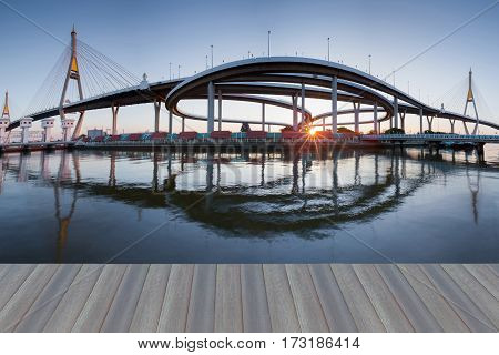 Opening wooden floor panorama Suspension bridge connect to highway intersection river front after sunset