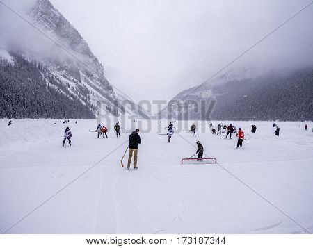 LAKE LOUISE, CANADA - FEB 19: Tourists enjoy a game of ice hockey on frozen Lake Louise in Banff on February 19, 2017 in Alberta, Canada. Lake Louise is a famous summer and winter destination.