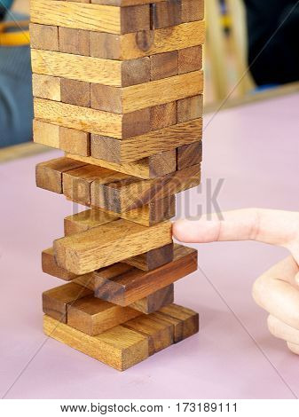 Businessman gambling removing wooden block on a tower. planning risk and strategy in business