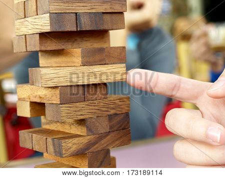 Hand removing blocks from a tower.Planning risk and strategy in business concept