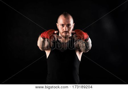 Fighter show into the camera. Man with muscular body and tattoo in black t-shirt on dark background. Showing concept.