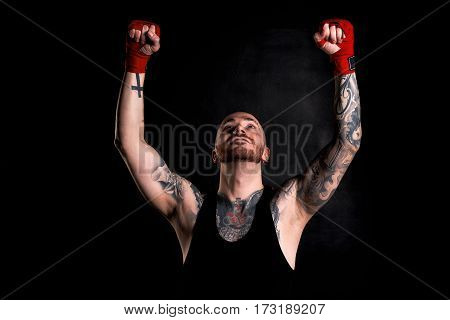 Victory concept. Fighter win the round of battle. Portrait of tattooed body guy in black t-shirt on dark background with red bandages.
