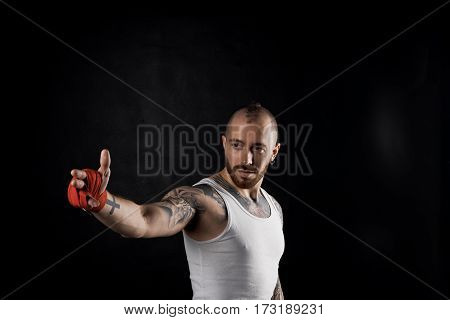 Fighter show by finger. Bearded man point the way. Sport concept with strong body guy in white t-shirt. Copy space for advertising fitness pruduct.