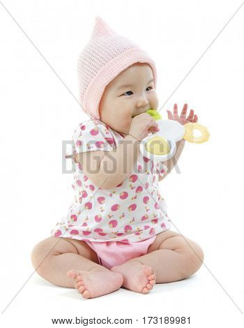 Portrait of full length beautiful Asian baby girl in pink clothes biting teething toy, isolated on white background.