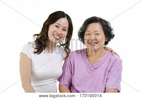 Portrait of Asian senior mother and adult daughter smiling and looking at camera, isolated on white background.