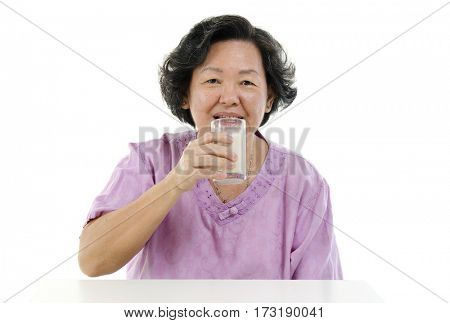 Portrait of happy Asian senior adult woman drinking a glass soy milk, isolated on white background.