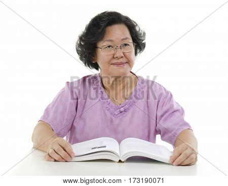 Wisdom Asian senior adult woman reading book, isolated on white background.