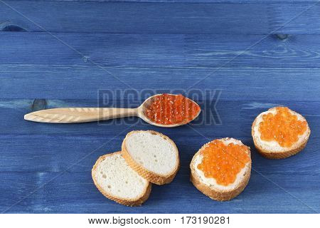 Red caviar toasts and wooden spoon on blue background