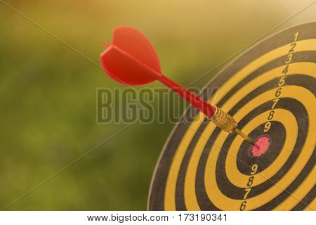 Red dart arrow with over blurred green background. target of dartboard . metaphor to target business concept.