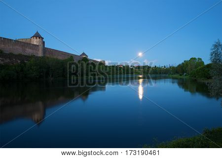 August twilight at the walls of the Ivangorod fortress. Border river Narva, Russia